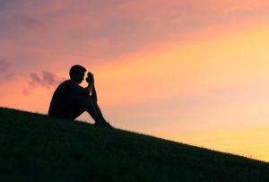 Silhouette of man praying at sunset